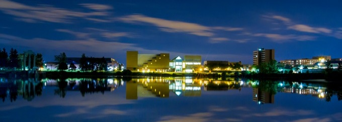u b center for the arts at night from across lake lasalle